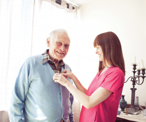 Care giving nurse providing Personal Home Care Services to elderly man in his own home helping him to age in place