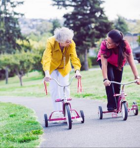 An elderly lady having fun riding a scooter for transportation with her nurse next door care giver