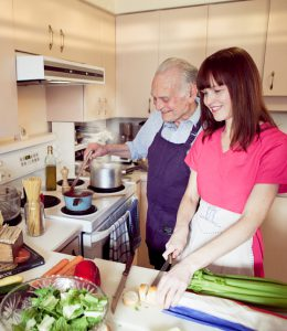 Care giver helping an elderly man prepare a meal in his own home making it possible for him to stay living in his own home