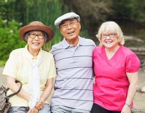 Elderly couple with their trusted nurse next door care giver on an outing to a park
