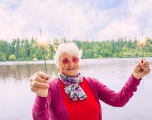elderly lady holding sparklers celebrating HappierAgeing with Nurse Next Door home care