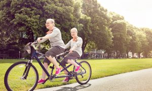 two elderly ladies riding a bike being active, healthy and happy with Nurse Next Door Home Care Agency