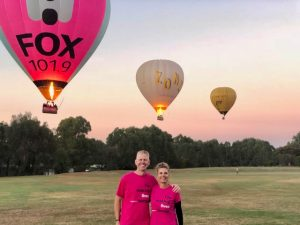 Nurse Next Door Dreams Project organisers with hot air balloons floating in sky in background