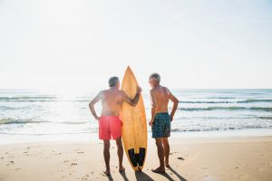 older men surfing at the beach