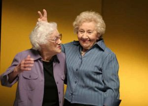 two elderly female friends have fun posing for the camera