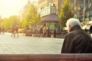 elderly old senior man sitting alone on a bench
