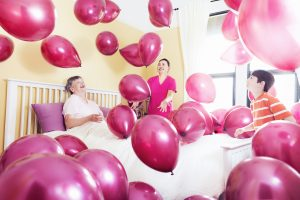 older person in bed surrounded by nurse, grandson and lots of pink balloons to focus on happiness