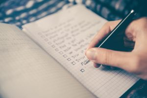 a picture of a hand writing a to do list in a notebook