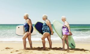 3 older women on the beach with their surfboards under their arms