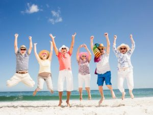 6 older people jumping on the beach, celebrating life